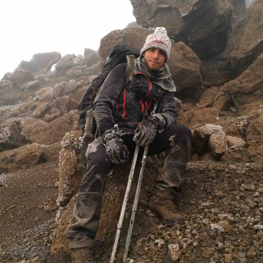 Francois climbing the Kilimanjaro with head on and walking sticks