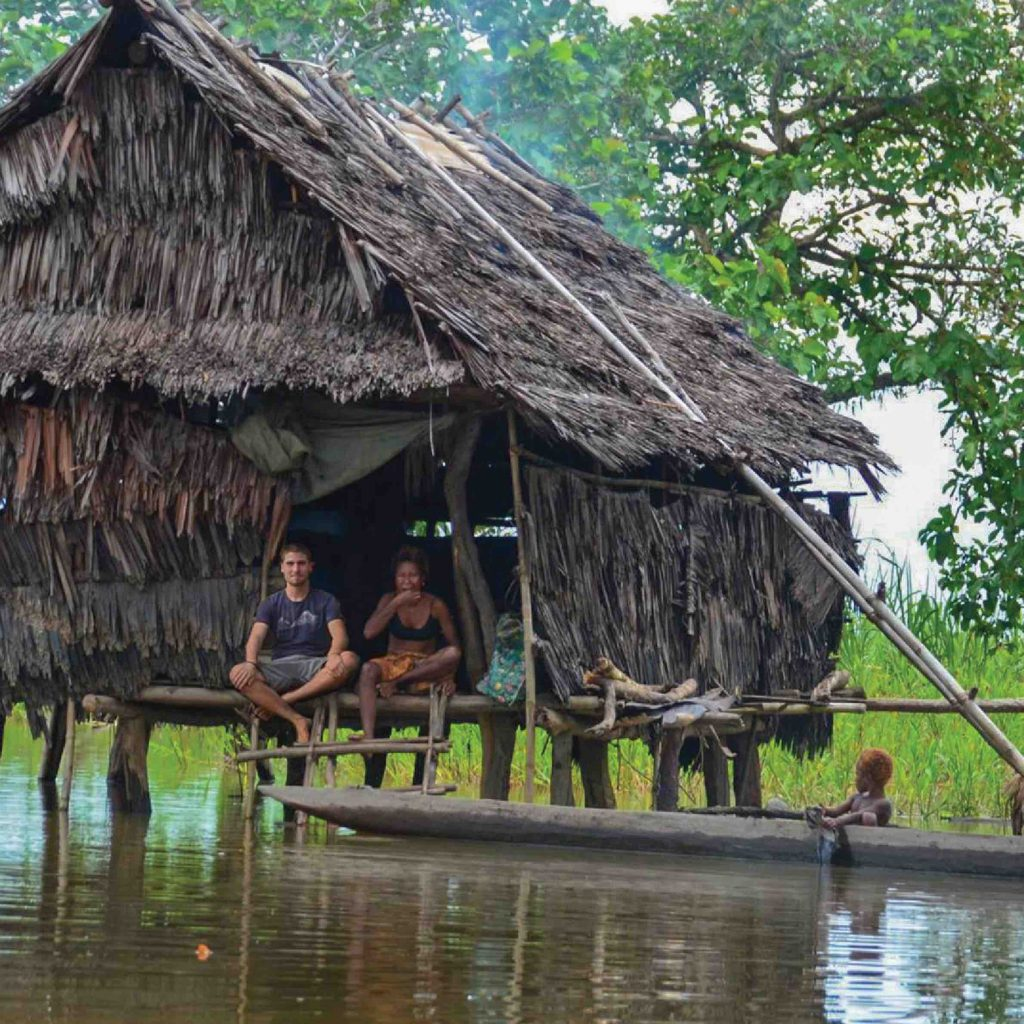 Francois in Papua New Guinea sitting in front of a wooden house at the riverside with a woman