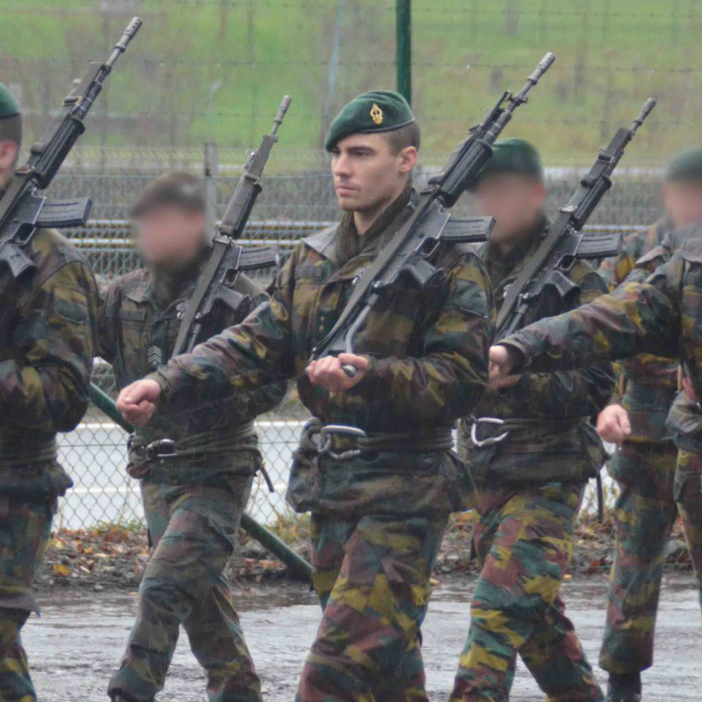 Francois in the army walking with hus gun and green baret