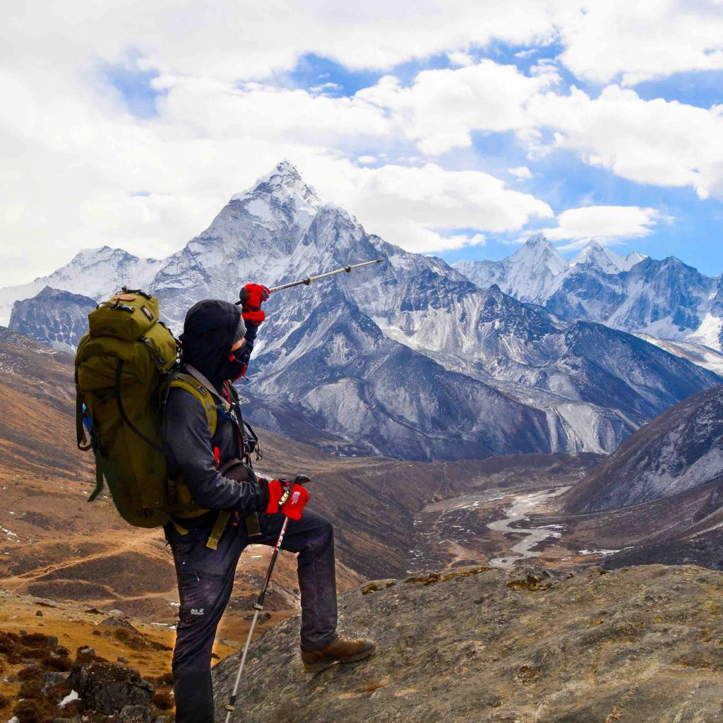 Francois pointing at the Mount Everest with hiking clothes and a big backpack in Nepal