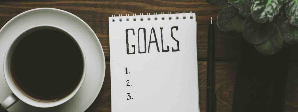 Coffee and paper with goals written on it