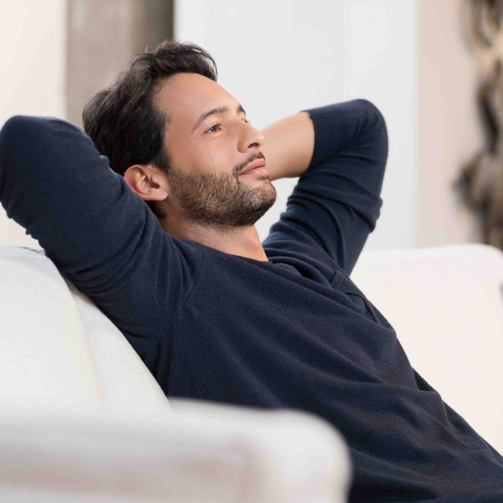 Man with blue shirt on white couch sitting, looking happy and thinking