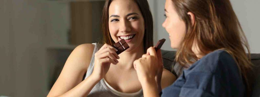 Two women laughing and sitting on the couch eating chocolate because they are hungry
