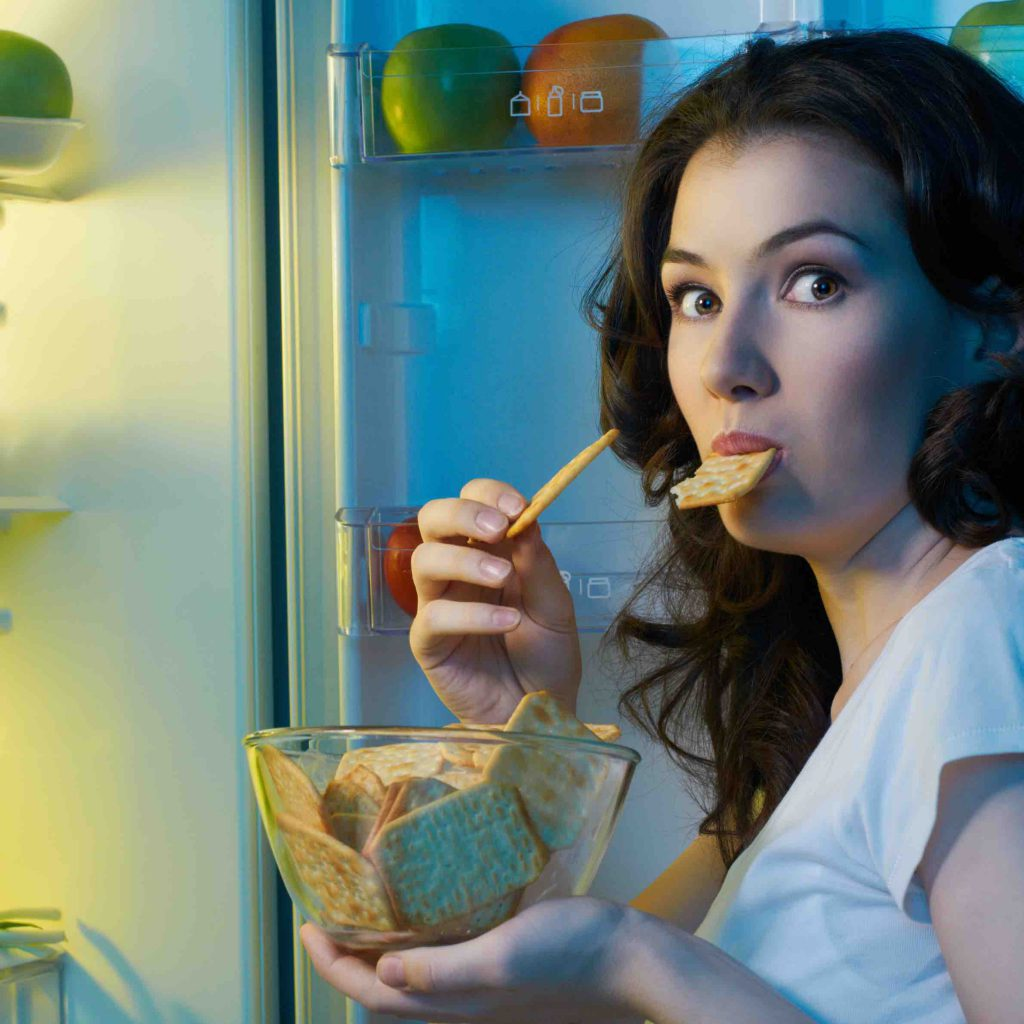 Woman eating cookies from the fridge with a bowl in the hand full of cookies