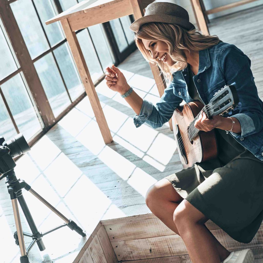 Woman playing guitar in front of camera in a nicely open space
